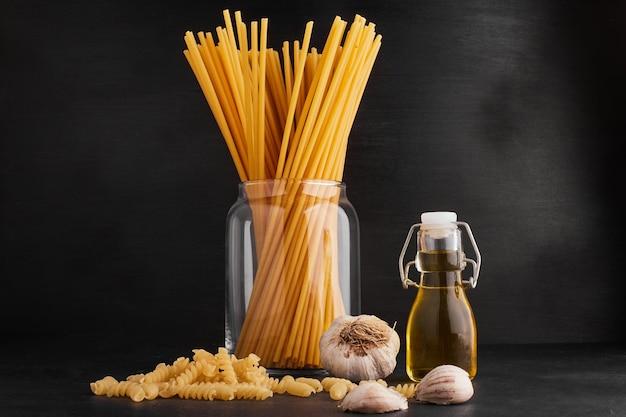 Spaghetties in een glazen beker met knoflookteentjes en olijfolie.