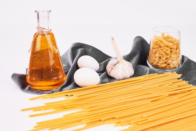 Spaghetties met een fles olie en ingrediënten.