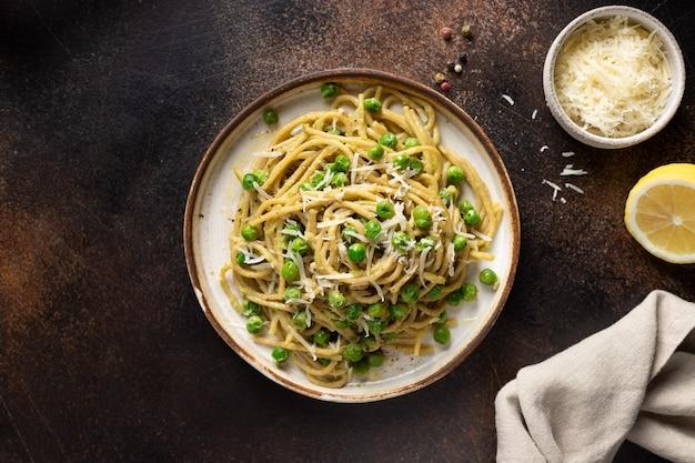 Spaghettis met groene erwten en avocado in een bord, met kaas en een donkere houten achtergrond van citroen