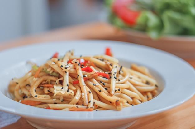 Spaghettischotel met wokgroenten en verse salade in een restaurant. detailopname.