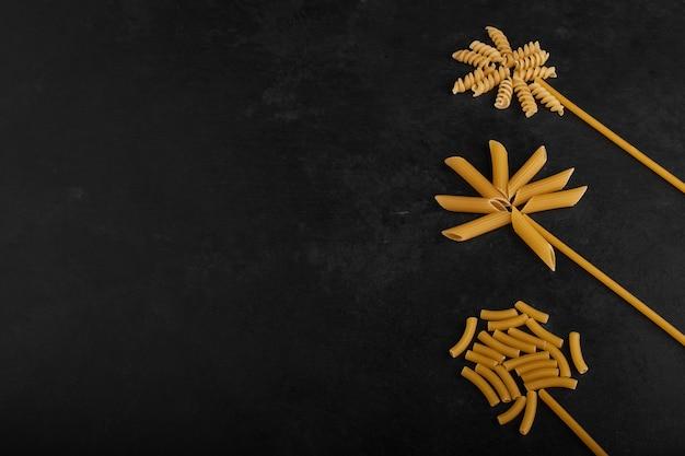 Spaghettistokken en pasta's in bloemvorm op zwarte achtergrond.