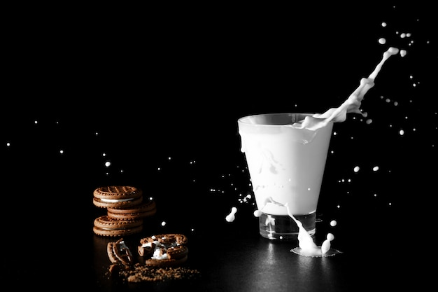 Spalsh in glas melk en chocoladekoekjes op zwarte achtergrond