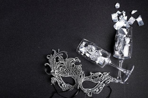 Spangles verspreid uit glazen met masker op zwarte tafel