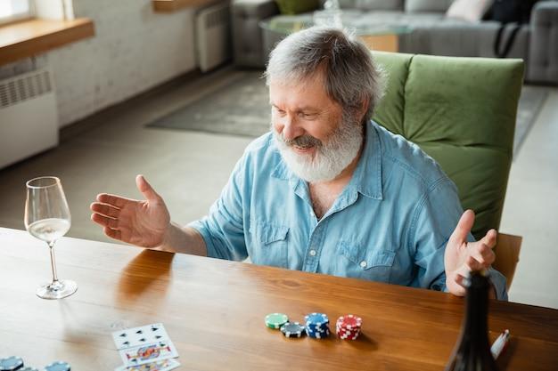 Spannend. gelukkig volwassen man speelkaarten en wijn drinken met vrienden.
