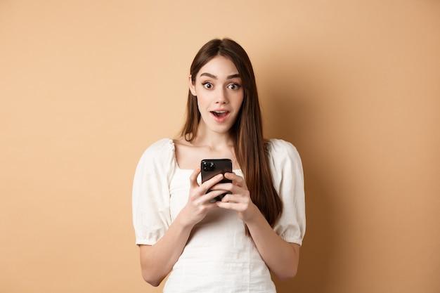 Spannend nieuws aan de telefoon. verbaasde jonge vrouw zegt wow na het lezen van online aankondiging op smartphone, staande op beige.