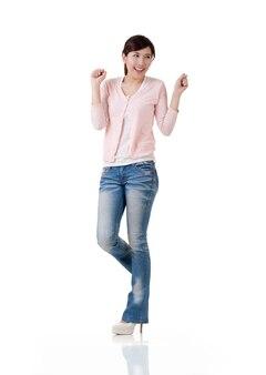 Spannende aziatische vrouw voelt zich vrij en verrast, volledig lengteportret met reflectie in studio witte achtergrond. Premium Foto