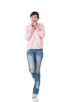 Spannende aziatische vrouw voelt zich vrij en verrast, volledig lengteportret met reflectie in studio witte achtergrond.