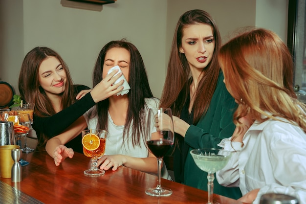 Spanning. vriendinnen met een drankje aan de bar. ze zitten aan een houten tafel met cocktails. ze dragen vrijetijdskleding. vrienden die een huilend meisje troosten en kalmeren Gratis Foto