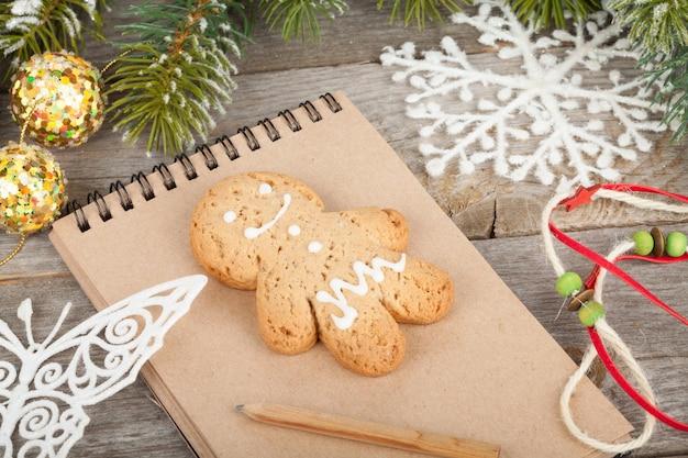 Spar kerstboom bedekt met sneeuw, decor en blanco notitieblok op houten plank achtergrond