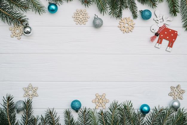 Spar kerstboom met decoratie en glitters op houten achtergrond. kerst achtergrond op het witte houten bureau