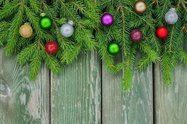 Spar kerstboom takken met kleurrijke decoratie op groene houten achtergrond. ruimte kopiëren, bovenaanzicht