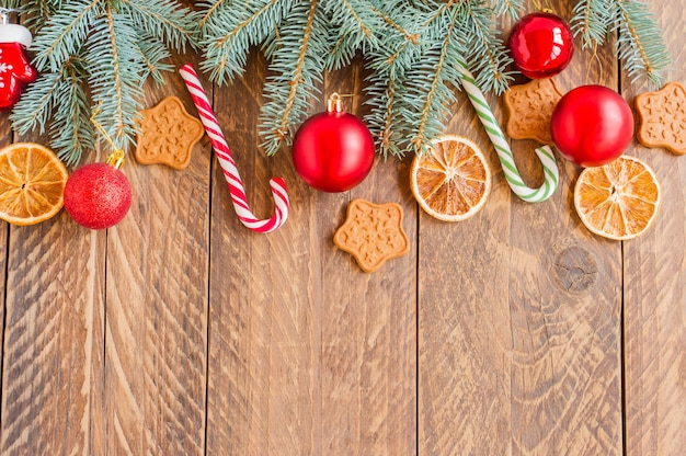 Spar-kerstboomtakken met kerstballen, snoeprietjes, droge sinaasappels en stervormkoekjes op houten ondergrond met kopieerruimte.