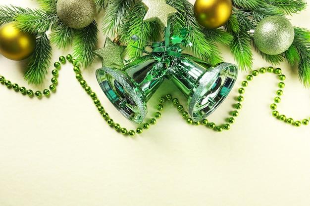 Spar kerstboomtakken met klokken, kralen en speelgoed op papier oppervlak