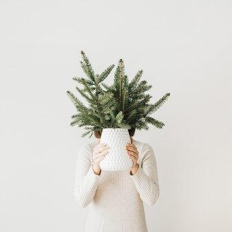 Spar takken bos in vrouwelijke hand op wit oppervlak.