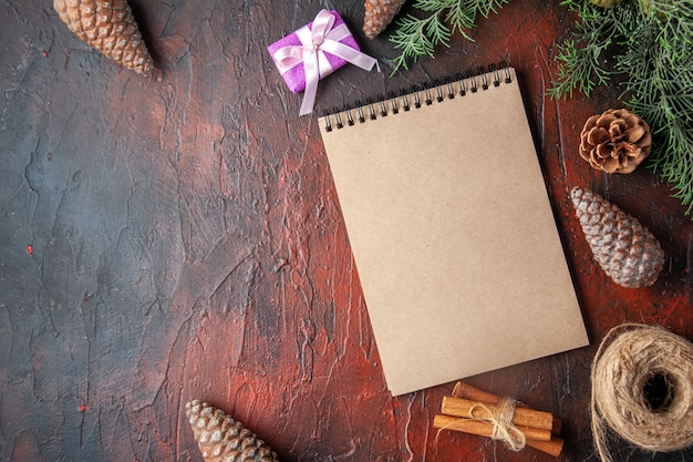 Spar takken decoratie accessoires conifer kegels cadeau en notitieboekje op donkere achtergrond