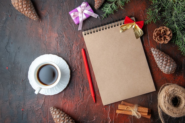 Spar takken decoratie accessoires conifer kegels geschenk en notebook een kopje zwarte thee op donkere achtergrond