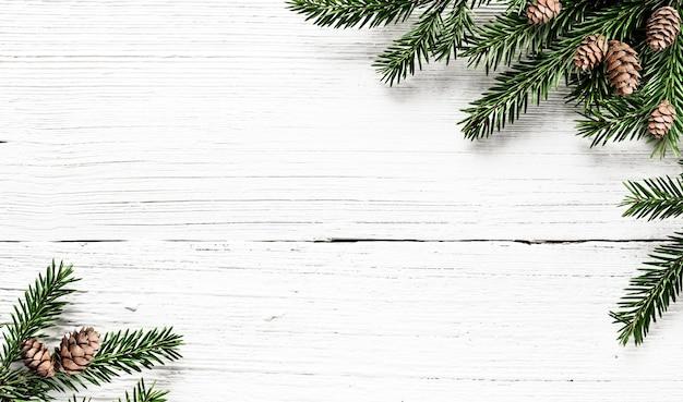 Spar takken en dennenappels op witte houten rustieke achtergrond. kerst compositie.