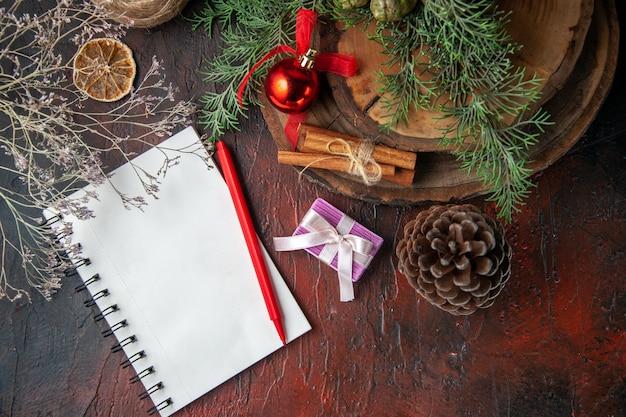 Spar takken en gesloten spiraal notitieboekje met pen kaneel limoenen conifer kegel en bal van touw op donkere achtergrond boven weergave