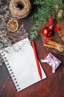 Spar takken en gesloten spiraalvormig notitieboekje met pen, kaneel, limoenen, naaldboom, en, bal, van, touw, op, donkere achtergrond