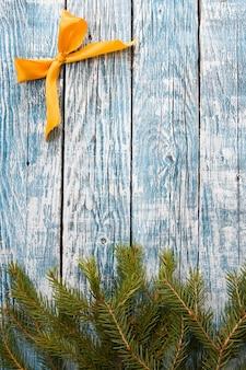 Spar takken en gouden lint strik op een blauwe houten achtergrond, kopie ruimte bovenaanzicht