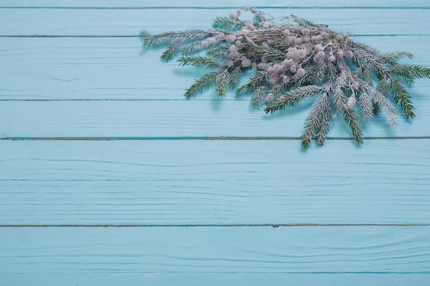 Spar takken in de sneeuw op blauwe houten oppervlak