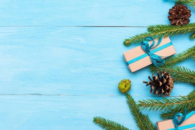 Spar takken met kegels op een lichtblauwe achtergrond en geschenken met kopie ruimte.