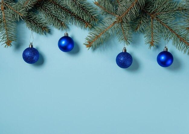 Spar takken versierd met blauwe kerstballen op een pastel blauwe achtergrond met kopie ruimte.