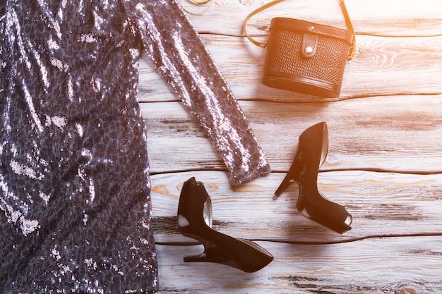 Sparkly jurk met zwarte schoenen donkere hakken en klassieke luxe handtas kleding op houten showcase qua...