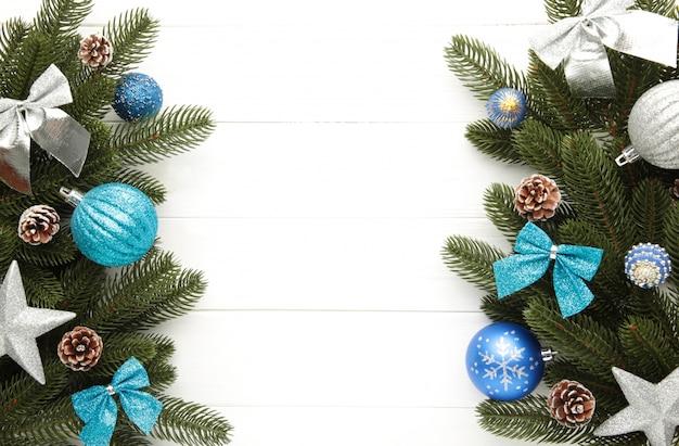 Sparrentakken met zilveren en blauwe kerstmisdecoratie op een witte achtergrond