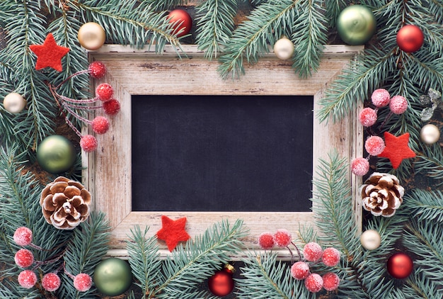 Spartakje versierd met kerstballen, bessen en sterren, zwart bord, tekst