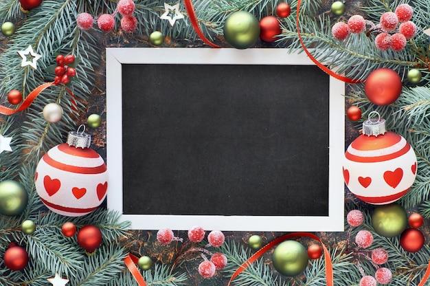Spartakje versierd met kerstballen, bessen en sterren, zwart bord