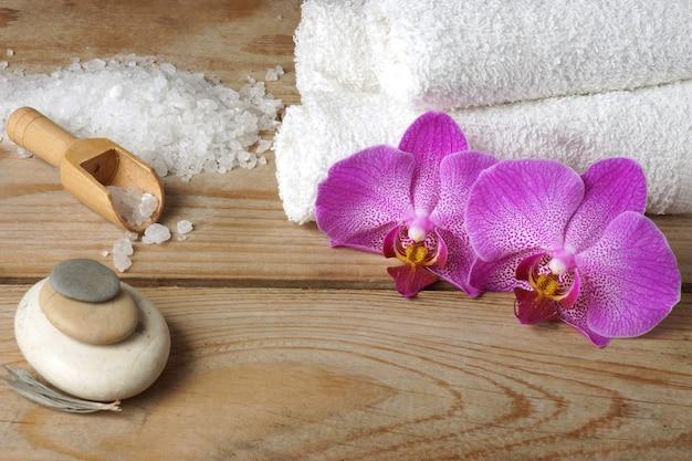 Spaset met witte handdoeken, zeezout en heldere orchideebloemen