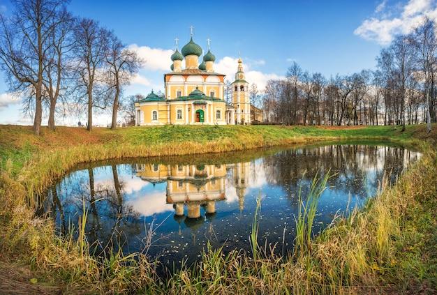 Spaso-preobrazhensky-kathedraal met een klokkentoren en weerspiegeling in het water van een vijver in het kremlin van uglich in de stralen van de herfstzon