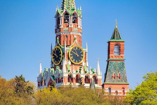 Spasskaya-toren van het kremlin van moskou tegen groene bomen en blauwe hemel