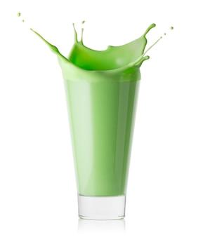 Spat in een glas groene smoothie of yoghurt