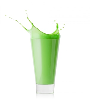 Spat in een groot glas groene smoothie of yoghurt