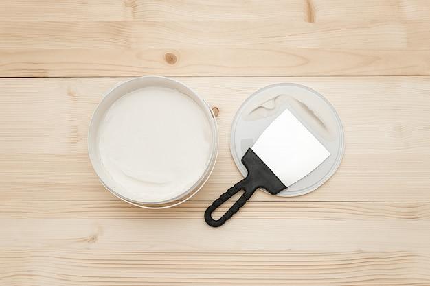 Spatel en een emmer witte stopverf op houten planken. bovenaanzicht kopieer ruimte