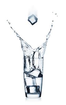 Spatten in glas met helder water en vliegende ijsblokjes