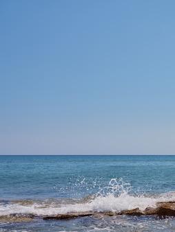 Spatten van de golven op de rotsen aan de kust van kreta.