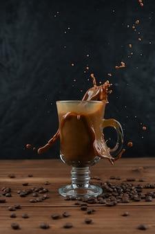 Spatten van koffie in glazen beker op donkere achtergrond.