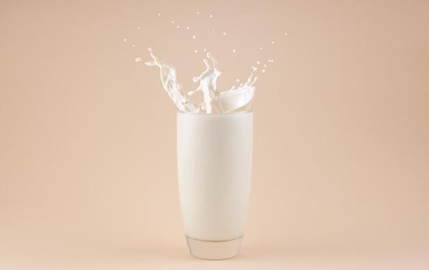 Spatten van melk in een glas geïsoleerd op beige background