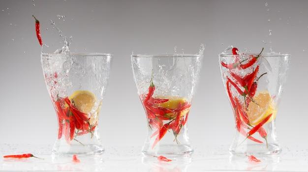 Spatten van water uit de roodgloeiende peper en citroen in een glas. collage. acute versheid concept