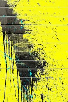 Spatten van zwarte verf op een gele muurachtergrond