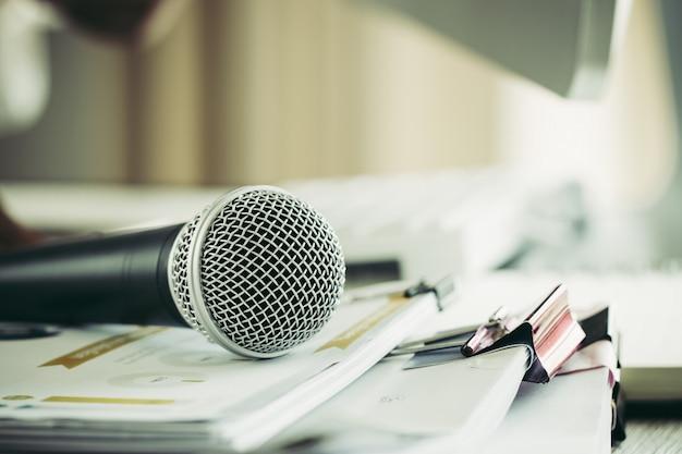 Speaker hold microfoon met papieren document op seminar voor spreken of lezing in de klas