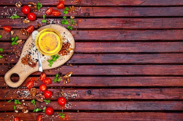 Specerijen, cherrytomaatjes, basilicum en plantaardige olie op donkere houten tafel, bovenaanzicht