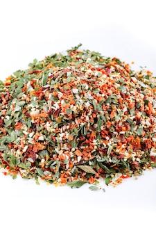 Specerijen. een handvol korrelige specerijen met groenten op een witte plaat. 12 groenten kruiden.