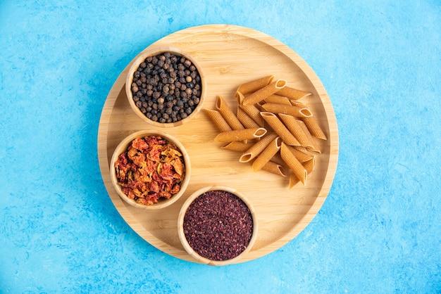 Specerijen en bruine pasta in houten dienblad over blauwe ondergrond.