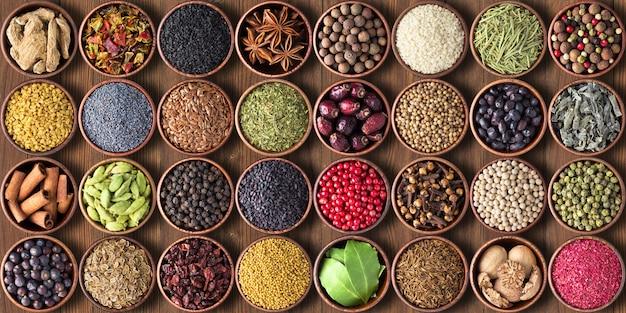 Specerijen en kruiden in bekers. kleurrijke kruiderijen behang