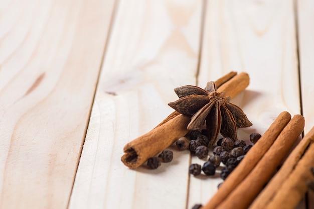 Specerijen en kruiden. ingrediënten voor eten en keuken. kaneelstokjes, anijssterren en zwarte peperkorrels.