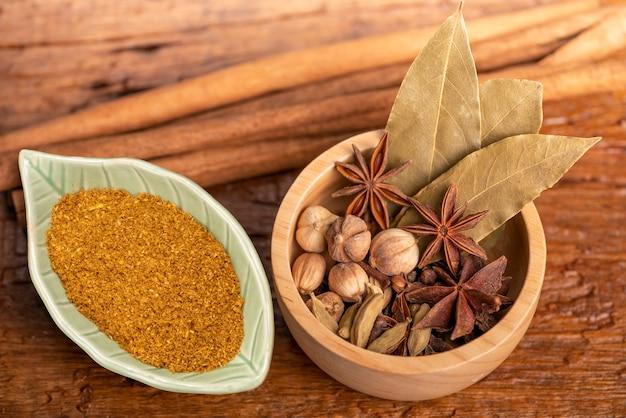Specerijen en kruiden ingrediënten voor het koken kerrie in houtslag, kerriepoeder, kruidnagel, kardemom, kaneel.